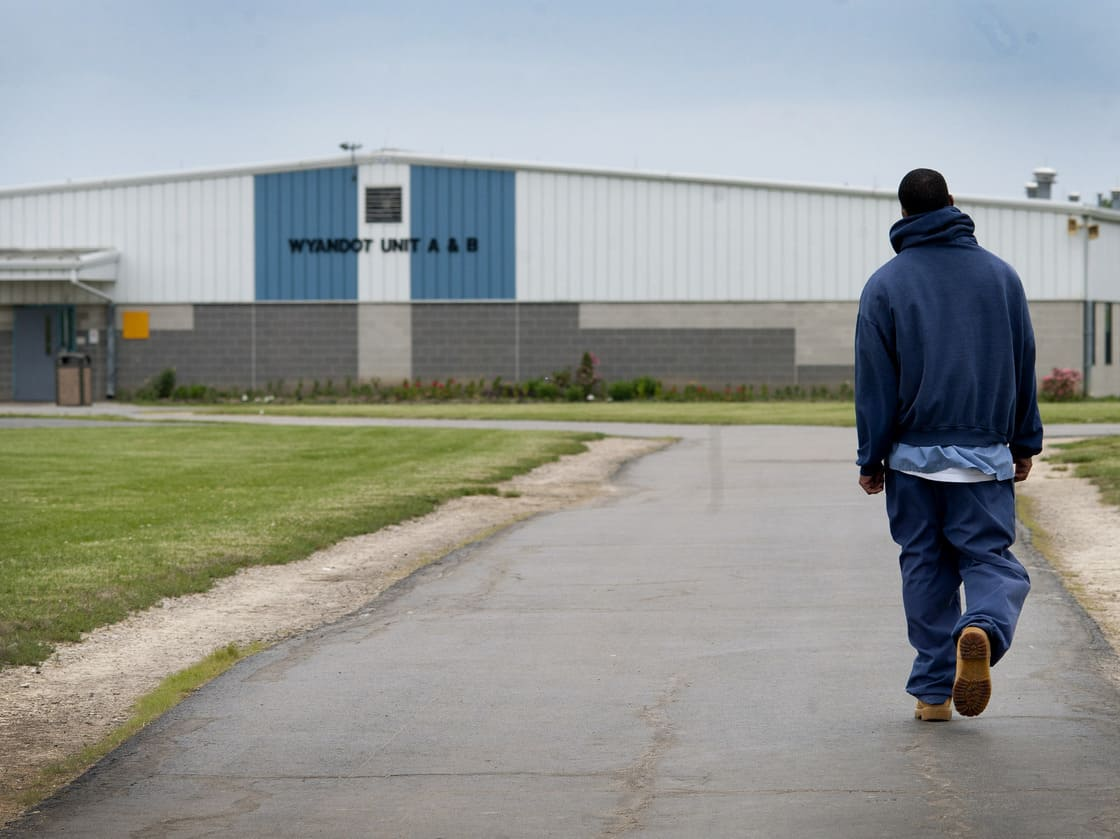 An inmate walks through the yard at the North Central Correctional Institution in Marion, Ohio, which recently switched to private management